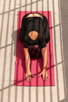 High view woman sitting in yoga position