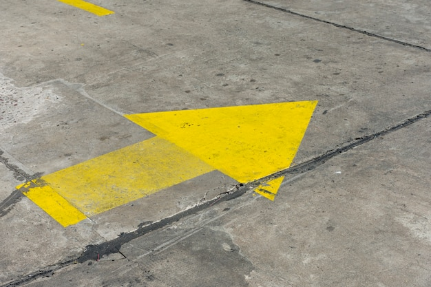 High view yellow painted arrow in the streets