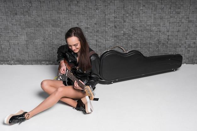 Высокий вид молодая женщина играет на электрогитаре