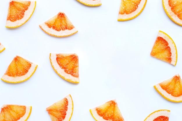 Высокое содержание витамина с. рама из ломтиков сочного грейпфрута на белой поверхности.