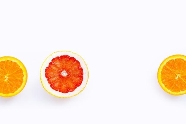 Высокое содержание витамина с, сочное и сладкое. свежий апельсин и грейпфрут на белой поверхности. копировать пространство