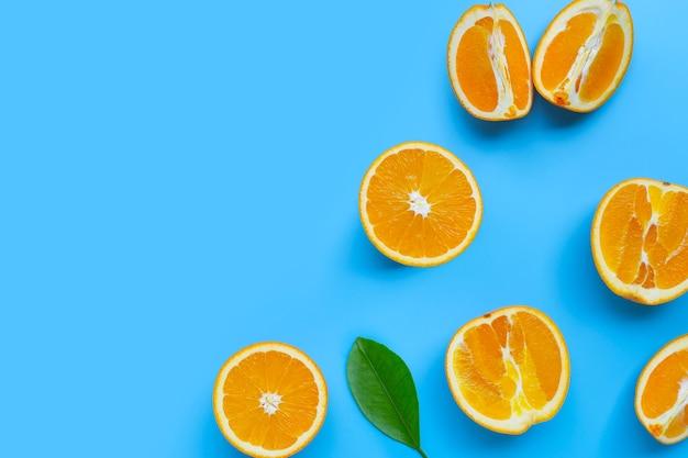 高ビタミンc、ジューシーで甘い。青の背景に新鮮なオレンジ色の果物。上面図