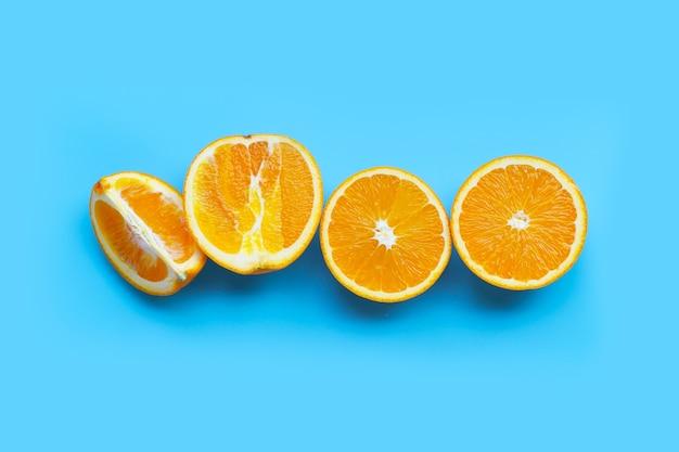Высокое содержание витамина с, сочное и сладкое. свежие оранжевые фрукты на синем столе. вид сверху