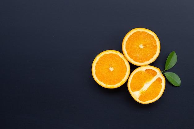 Высокое содержание витамина с, сочное и сладкое. свежие оранжевые фрукты с зелеными листьями на темном деревянном столе.