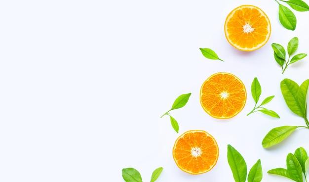 Высокое содержание витамина с, сочное и сладкое. свежие оранжевые плоды с зелеными листьями на белом.