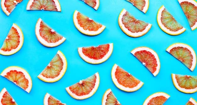 Высокое содержание витамина c. сочные дольки грейпфрута на синем фоне. вид сверху