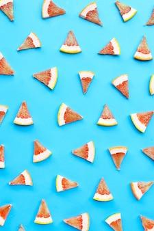 Высокое содержание витамина с. сочные дольки грейпфрута на синей поверхности.