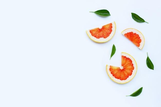 Высокое содержание витамина с. сочные дольки грейпфрута на белой поверхности.