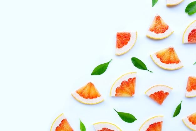 Высокое содержание витамина c. сочные дольки грейпфрута на белой стене.