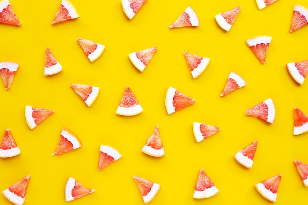 Высокое содержание витамина с. сочные дольки грейпфрута на желтой поверхности.