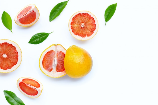 High vitamin c. juicy grapefruit slices with green leaves on white background.