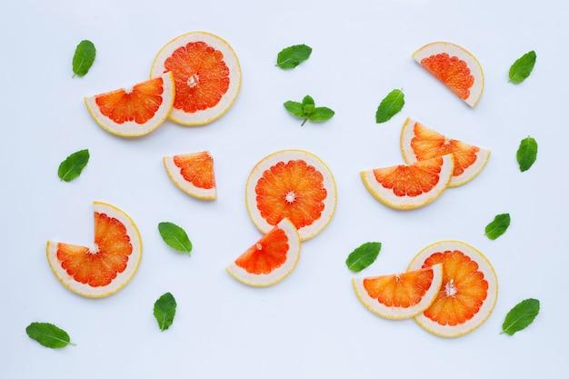Высокое содержание витамина с. сочные дольки грейпфрута с листьями мяты на белой поверхности.