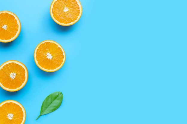 High vitamin c, juicy and sweet. fresh orange fruit  on blue background. top view