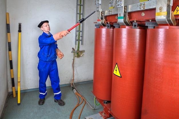 Детектор высокого напряжения, инженер-электрик, использующий тестер высокого напряжения для безопасности.