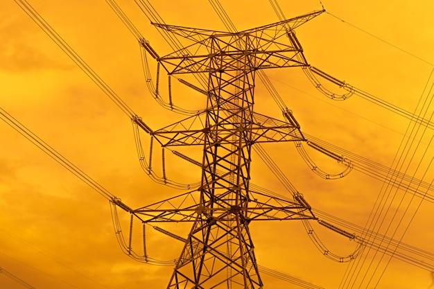 Электрический столб высокого напряжения с распределительной станцией инженера-электрика линии электропередач на закате.