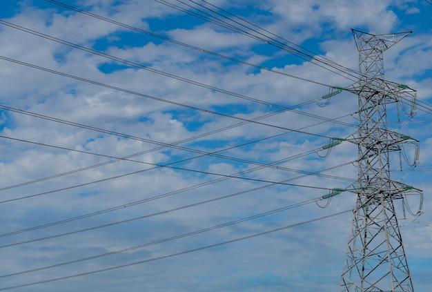 푸른 하늘과 구름에 대 한 고전압 전기 철 탑과 전선. 전기 철탑의 밑면. 와이어 케이블이있는 고전압 그리드 타워.
