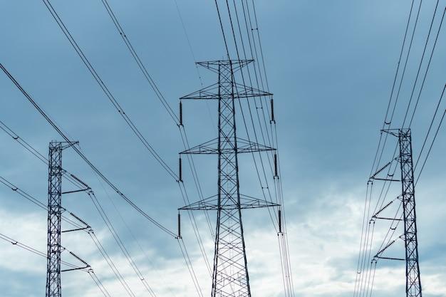 Электрический пилон высокого напряжения и электрический провод против голубого неба и облаков.