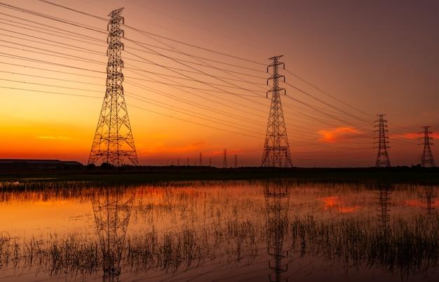 高電圧電気パイロンと夕焼け空と電線。電柱。力とエネルギーの概念。工場近くの田んぼ畑にワイヤーケーブルを備えた高圧グリッドタワー。
