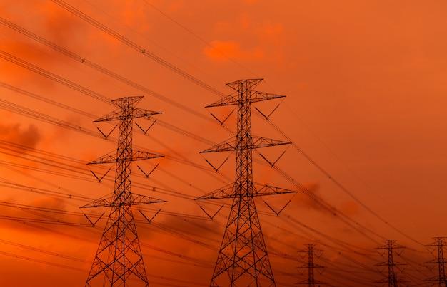 Высоковольтная электрическая опора и электрический провод с небом захода солнца. опоры электричества. концепция власти и энергии. высоковольтная высоковольтная опора с проводным кабелем. красивое красно-оранжевое небо захода солнца. инфраструктура.