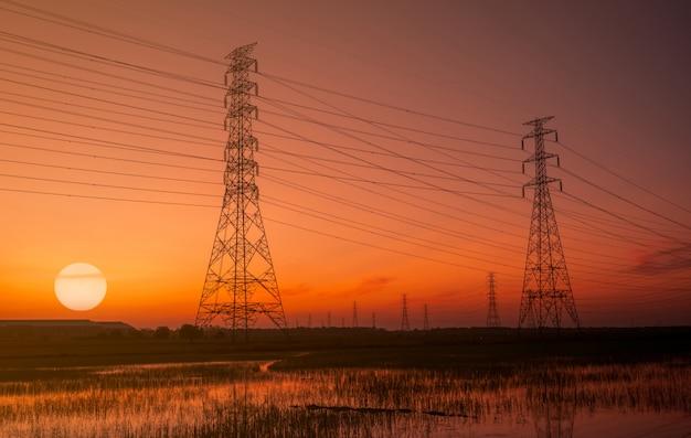 Высоковольтная электрическая опора и электрический провод с небом захода солнца.