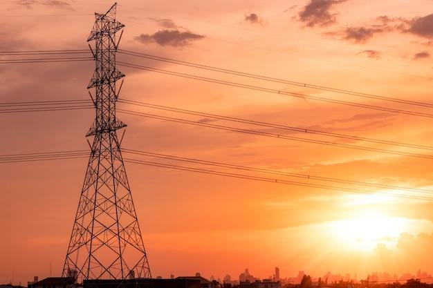 일몰 하늘과 도시 경관이 있는 고압 전기 철탑 및 전송 라인. 전기 철탑. 고전압 그리드 타워입니다. 도시 지역 사회에 전기를 분배하기 위한 고압 전주.