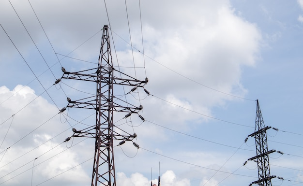 고전압 전기 타워입니다. 푸른 하늘에 원형 구름이 있는 화창한 날 전력선과 전력 철탑. 고전압 송전선로를 지원합니다. 그들은 복잡한 강철 구조를 가지고 있습니다.