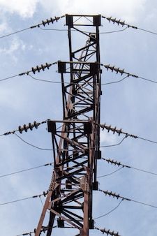 High voltage electrical tower. power lines and power pylons on a sunny day with circular clouds in the blue sky. high voltage power transmission line supports. they have a complex steel structure.
