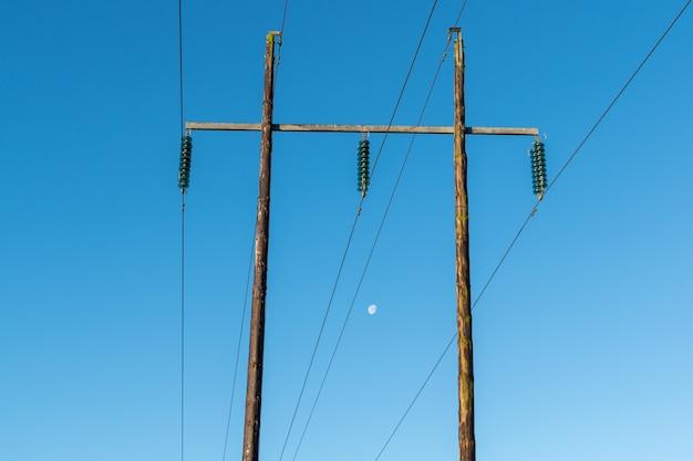 Линии электропередач высокого напряжения на деревянных опорах против голубого неба с видимой луной в дневное время