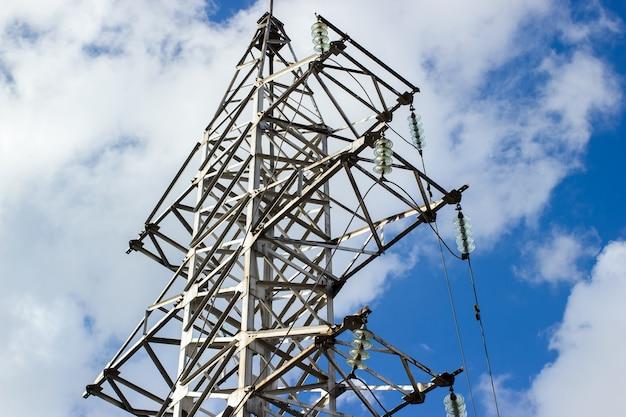 푸른 하늘과 구름 배경의 고전압 전기 철탑과 송전선