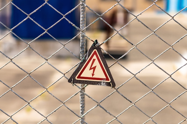 High voltage hazard warning sign on the fence