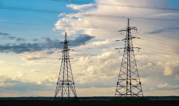 푸른 하늘에 구름이 있는 화창한 날 평평하고 농업적인 풍경에 고압선과 전력 철탑이 있습니다.