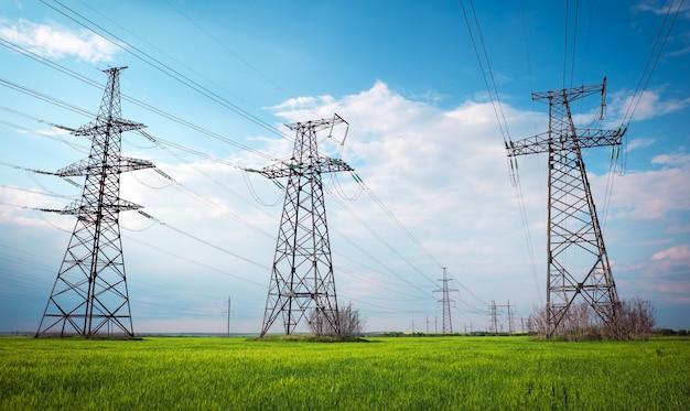 Линии высокого напряжения и опоры электропередач в плоском и зеленом сельскохозяйственном ландшафте в солнечный день с облаками в голубом небе. пасмурно и дождливо. пшеница растет