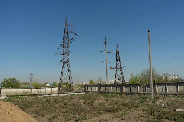 맑고 푸른 하늘이 있는 화창한 날 산업 지역의 고압선과 전력 철탑.