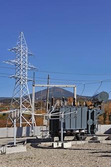 Масляный силовой трансформатор высокого напряжения на электрической подстанции на голубом небе