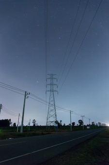 High voltage pole in night time with star on sky background