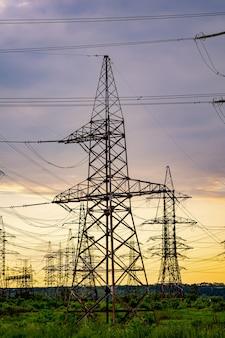 고전압 포스트. 일몰 배경에 대해 고전압 철탑입니다. 에너지 및 산업화 개념입니다. 선택적 초점