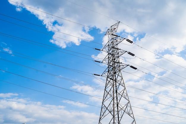 高電圧ポスト。青い空と雲の上の高電圧タワー