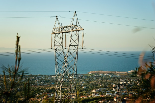 High voltage post or high voltage tower, view of city on background