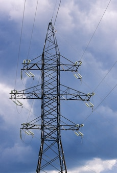 High voltage post or high voltage tower with cable on a dark blue cloud sky background