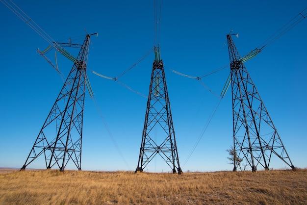 Столбы высоковольтной линии электропередач в поле в голубом небе