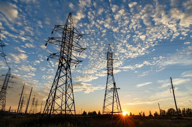 Высоковольтная линия электропередач поддерживает на закате.