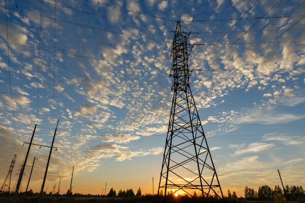 High voltage power line supports at sunset