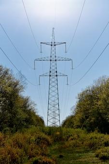 Линии электропередач высокого напряжения против неба в солнечном свете