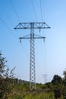 Линии электропередач высокого напряжения над полем в солнечный день на фоне голубого неба.