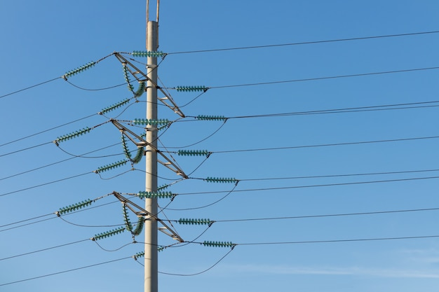 High voltage power pole against the blue sky