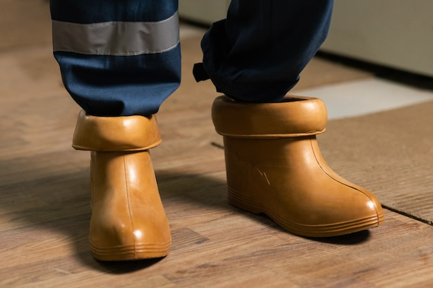 High voltage power station electrician wears rubber boots electrical technician