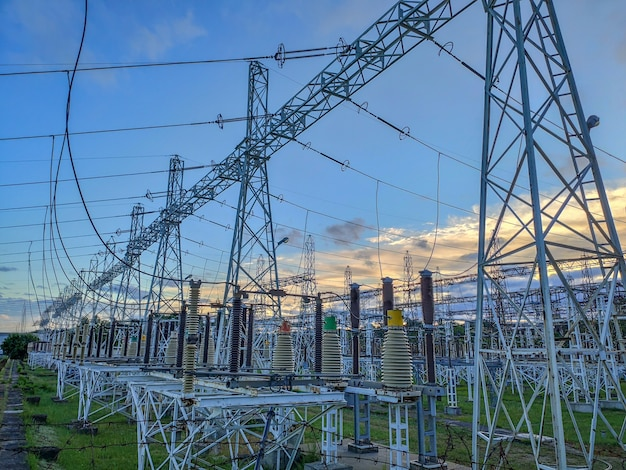High voltage power transformer substation. hight voltage tower with blue sky and sunset.