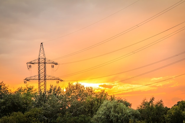 일몰 시 전기 에너지 전선이 있는 고전압 송전탑
