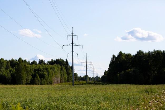 봄 여름 시골, 숲, 구름이 있는 푸른 하늘의 고전압 철탑