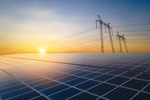 태양광 발전에서 전기를 전송하는 전력선이 있는 고전압 철탑은 일출 시 판매됩니다. 지속 가능한 에너지 개념의 생산.